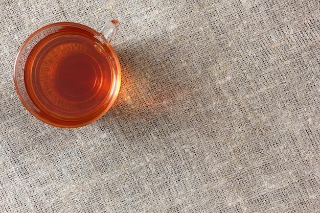 Szklany Przezroczysty Kubek Z Czarną Herbatą Na Szorstkim Płótnie Obrus, Widok Z Góry. Premium Zdjęcia