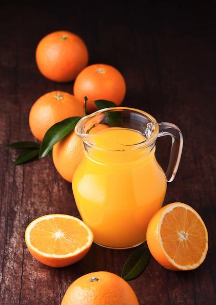 Szklany Słój Organicznie świeży Sok Pomarańczowy Z Surowymi Pomarańczami Na Ciemnym Drewnianym Tle Premium Zdjęcia