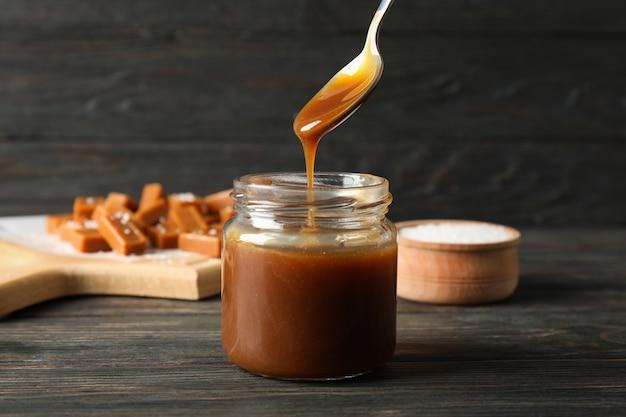 Szklany Słój Z Solonym Karmelem I Cukierkami Na Drewnianej Przestrzeni, Przestrzeń Dla Teksta Premium Zdjęcia