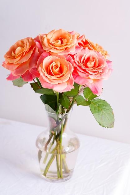 Szklany Wazon Z Pięknym Bukietem świeżych Kwiatów Naturalnych Róż Na Stole Pokrytym Białym Materiałem Na Jasnoszarej ścianie. Premium Zdjęcia