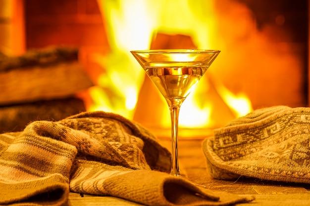 Szkło martini przeciw wygodnemu kominkowemu tłu Premium Zdjęcia