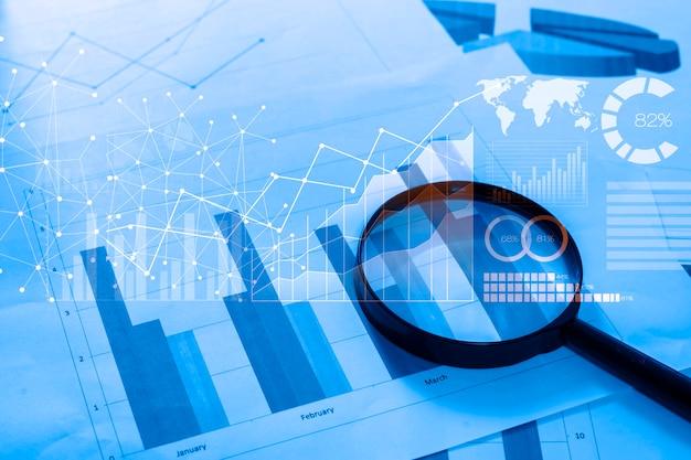 Szkło Powiększające I Dokumenty Z Danymi Analitycznymi Leżące Na Stole Premium Zdjęcia