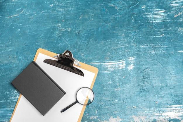 Szkło powiększające i notatnik na drewnianym stole Premium Zdjęcia