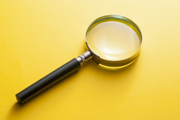 Szkło powiększające leżące po przekątnej na żółto Premium Zdjęcia
