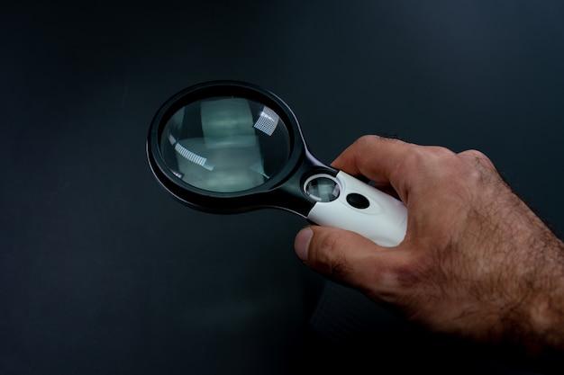 Szkło Powiększające W Dłoni Na ścianie Premium Zdjęcia