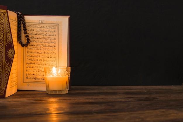 Szkło Ze świecą W Pobliżu Otwartego Koranu Darmowe Zdjęcia