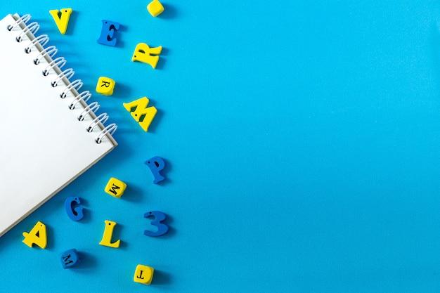 Szkolne dostawy na niebieskim tle. koncepcja dnia szkoły i nauczyciela. drewniane litery na stole z miejsca kopiowania. Premium Zdjęcia