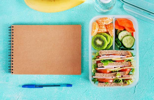 Szkolne Pudełko Na Lunch Z Kanapkami, Warzywami, Wodą I Owocami Na Stole. Pojęcie Zdrowych Nawyków żywieniowych. Leżał Płasko. Widok Z Góry Premium Zdjęcia