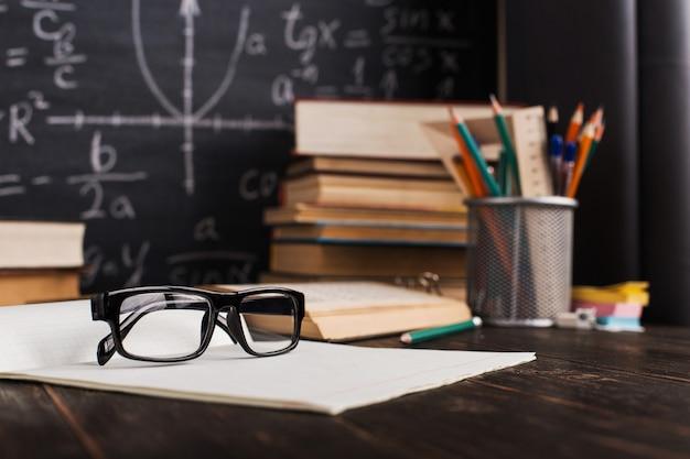 Szkolny biurko w sala lekcyjnej z książkami na tle kredowa deska z pisać formułami Premium Zdjęcia
