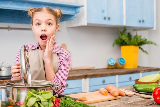 Szokująca Dziewczyna Otwiera Dekiel Kulinarny Garnek W Kuchni Patrzeje Kamerę Darmowe Zdjęcia