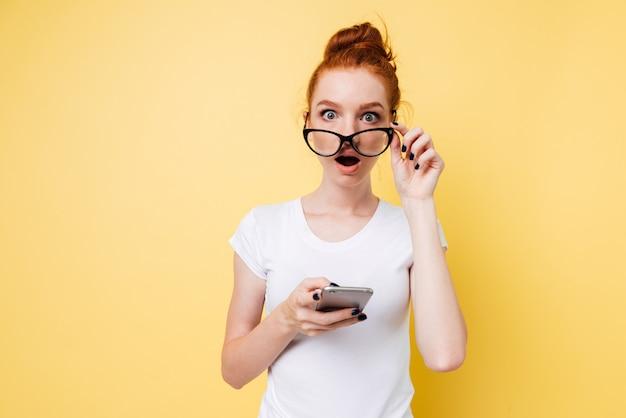 Szokująca Imbirowa Kobiety Mienia Smartphone I Patrzeć Przez Okularów Darmowe Zdjęcia