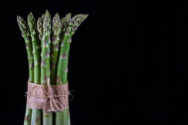 Szparag. Bukiet świeżych Zielonych Szparagów Wiązanej Na Czarnym Tle. Premium Zdjęcia