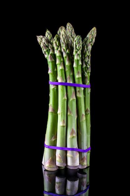 Szparag. Pęczek świeżych Zielonych Szparagów Przywiązanych Na Czarnej ścianie Premium Zdjęcia