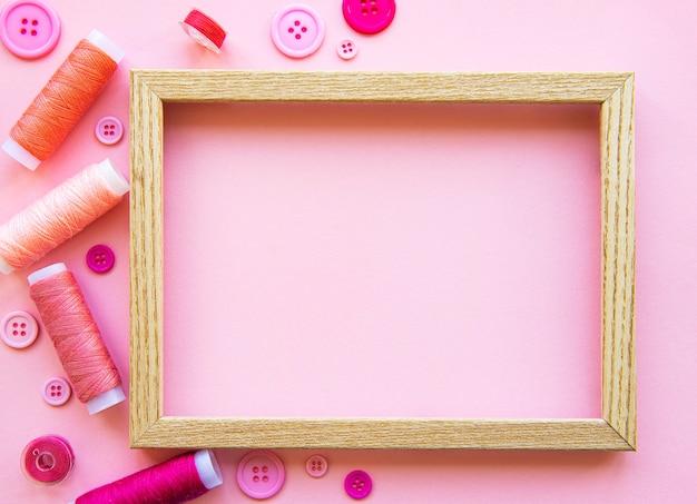 Szpule Z Nicią I Guziki W Różowych Odcieniach Na Różowym, Płaskim Ułożeniu Premium Zdjęcia