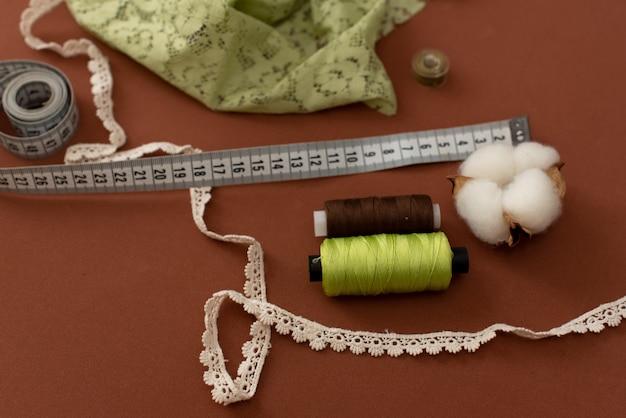 Szpulki do maszyn do szycia z nożyczkami złota (mosiądz) i czarny jedwabisty tkaniny na starym stole roboczym grungy. stół roboczy krawca. wytwarzanie tkanin lub delikatnych tkanin. Premium Zdjęcia