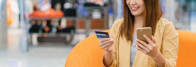 Sztandar Azjatycka Kobieta Używa Kredytową Kartę Z Telefonem Komórkowym Dla Online Zakupy W Domu Towarowym Premium Zdjęcia