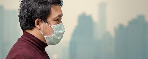 Sztandar azjatykci mężczyzna jest ubranym twarz maskę przeciw zanieczyszczeniu powietrza przy balkonem Premium Zdjęcia