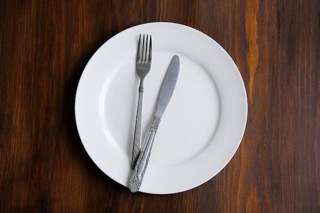 Sztućce na pustym białym talerzu, na drewnianym stole. pojęcie jedzenia. Premium Zdjęcia