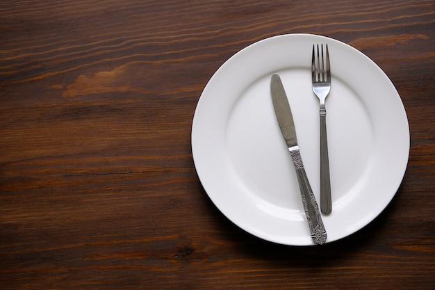 Sztućce na pustym białym talerzu. Premium Zdjęcia