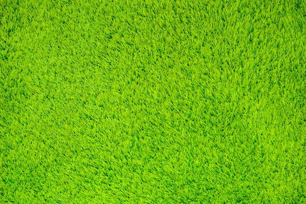 Sztuczna powierzchnia trawy na tle. Premium Zdjęcia