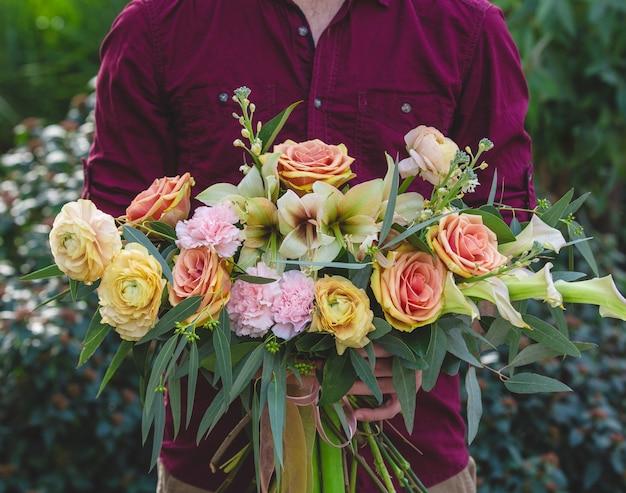 Sztuka kwiatowa, wieniec z mieszanych kwiatów w rękach mężczyzny Darmowe Zdjęcia