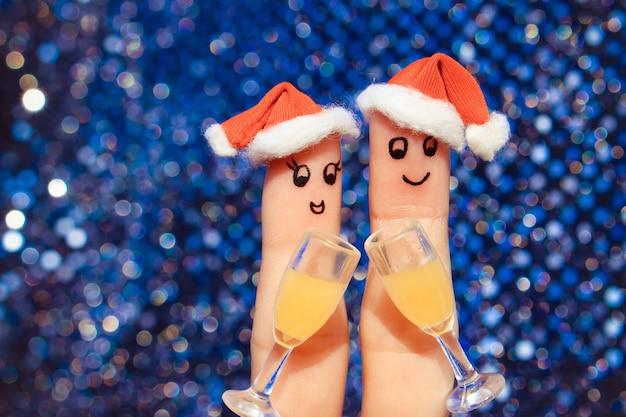 Sztuka palec szczęśliwej pary w kapeluszach nowego roku. Premium Zdjęcia