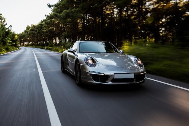 Szybka jazda mini coupe na drodze z włączonymi światłami przednimi. Darmowe Zdjęcia
