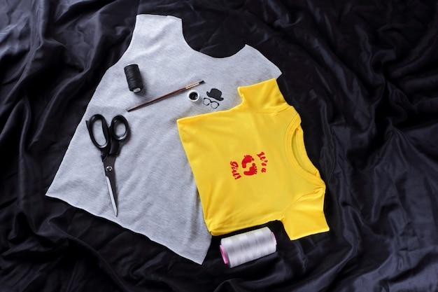 Szycie Koszulek Dziecięcych Z Ręcznie Robionym Rysunkiem. Szary I żółty Materiał W Ciemności Premium Zdjęcia