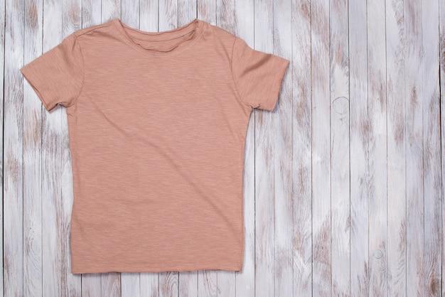 T-shirt Z Kolorowym Lakierem Z Miejscem Na Kopię. Makieta Koszulki, Układanie Na Płasko. Stylowy Drewniany Stół. Premium Zdjęcia