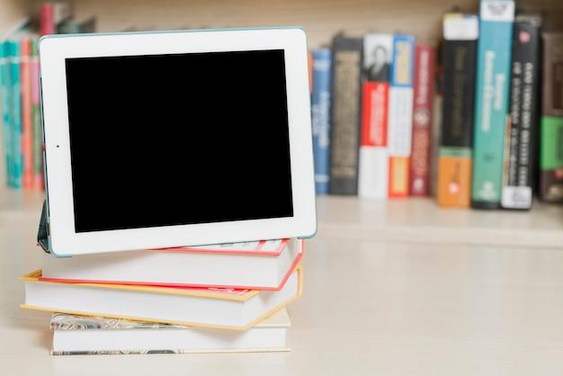Tablet i książek w pobliżu półki Darmowe Zdjęcia