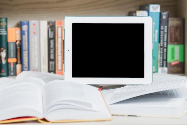 Tablet i otwarte książki w pobliżu regału Darmowe Zdjęcia