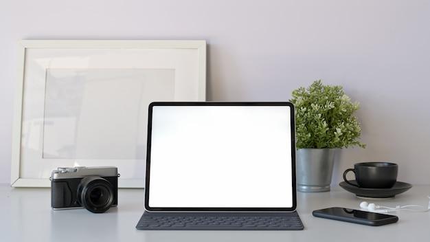 Tablet makieta biurowy z inteligentną klawiaturą na minimalny biały stół roboczy. Premium Zdjęcia