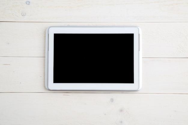 Tablet na drewnianym stole Premium Zdjęcia