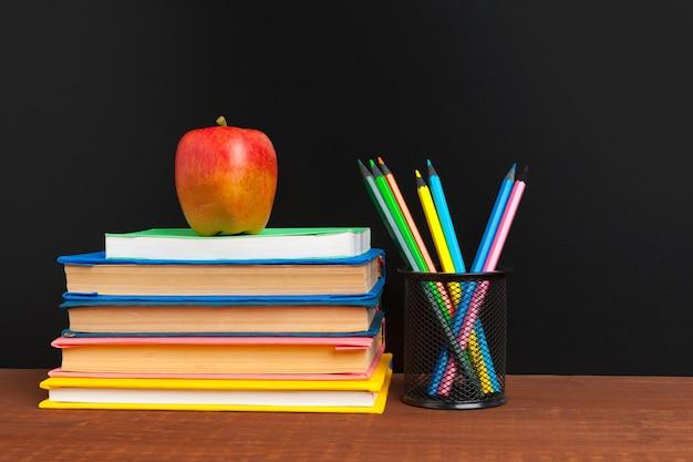 Tablica z książkami i jabłkiem na drewnianym biurku Premium Zdjęcia