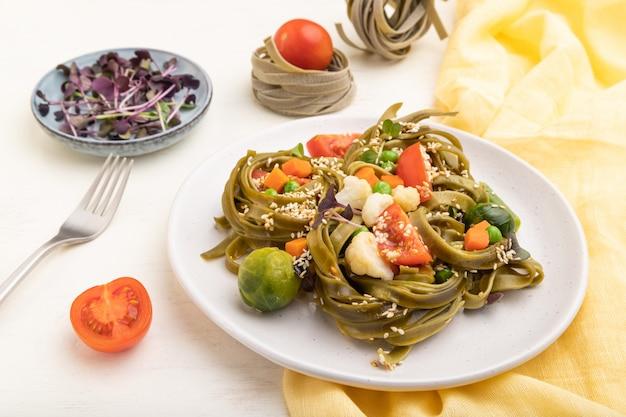 Tagliatelle Zielony Szpinak Makaron Z Pomidorów, Grochu I Mikrogreen Kapusty Na Białym Tle Drewnianych. Premium Zdjęcia