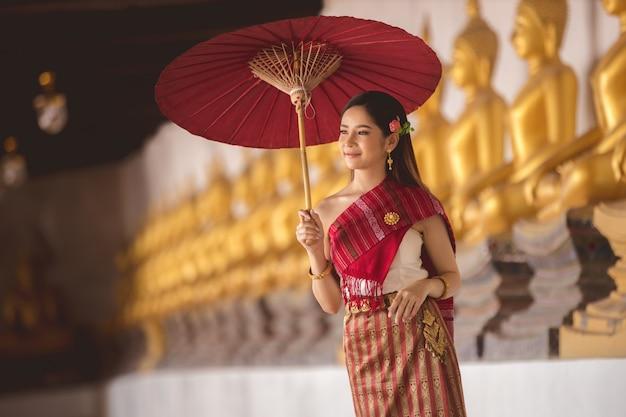 Tajlandzka dziewczyna w tradycyjnym tajlandzkim kostiumu z czerwonym parasolem w tajlandzkiej świątyni, tożsamości kultura tajlandia. Premium Zdjęcia