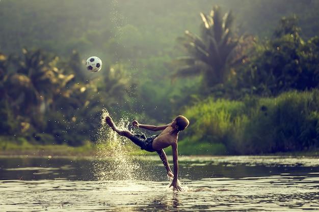 Tajlandzka Młoda Chłopiec Bawić Się Piłkę Nożną I Zasięrzutny Kopnięcie Na Zmierzchu. Premium Zdjęcia