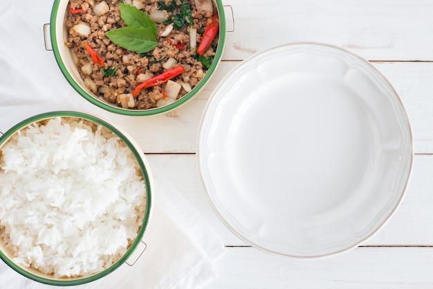 Tajlandzki karmowy imię ochraniacz ka prao, odgórnego widoku wizerunek rice z smażącą wieprzowiną z basilem opuszcza obok pustego naczynia na białym drewno stole Premium Zdjęcia