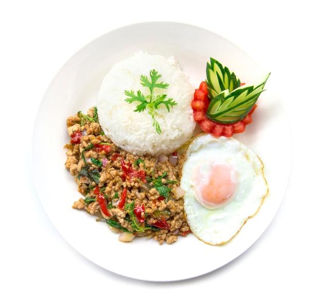 Tajskie jedzenie smażone na ostro wieprzowe pikantne i bazylia podawane z ryżem i jajkiem sadzonym i ogórkiem pomidorowym Premium Zdjęcia