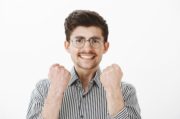 Tak, Zakończyliśmy Projekt Na Czas. Portret Przystojnego Dojrzałego Modela W Okularach I Koszuli W Paski, Unoszący Zaciśnięte Pięści, Pewny Siebie, świętujący Sukces I Zwycięstwo Nad Szarą ścianą Darmowe Zdjęcia