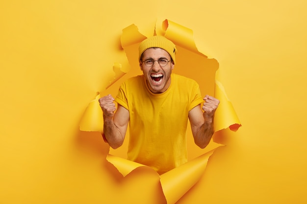 Tak, Zrobiliśmy To! Triumfujący, Pełen Emocji Mężczyzna Krzyczy Na Ulubioną Drużynę, Wrzeszczy Z Radości, Nosi żółtą Czapkę I Koszulkę Darmowe Zdjęcia