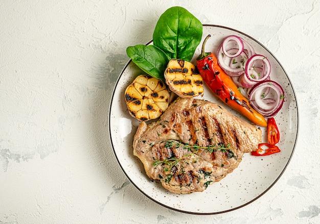 Talerz Grillowany Stek Wieprzowy Z Warzywami Na Betonowym Tle Premium Zdjęcia