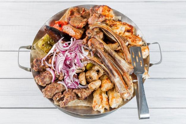 Talerz mięsny z pysznymi kawałkami mięsa, żeberkami, grillowanymi ziemniakami i pieczarkami z cebulą. Premium Zdjęcia