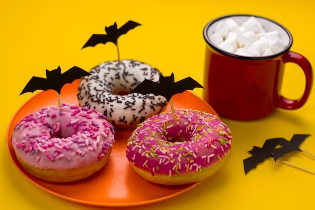 Talerz Z Pączkami Ozdobiony Nietoperzami Wyciętymi Z Papieru I Kubek Kakao Z Piankami Na Stole Na Imprezie Halloween Premium Zdjęcia