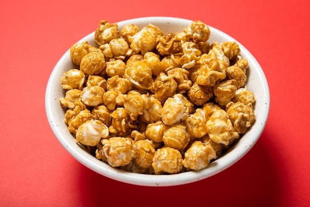 Talerz Z Popcornem Karmelowym Na Czerwonym Tle Premium Zdjęcia