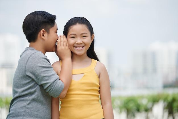 Talia portret azjatyckich dzieci patrzących w kamerę, chłopiec szepczący sekret swojemu gorlfriendowi Darmowe Zdjęcia
