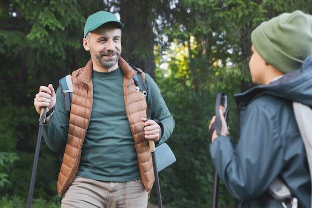 Talia Się Portret Szczęśliwego Ojca I Syna Wędrujących Razem I Rozmawiających Podczas Spaceru W Lesie Z Kijkami, Skopiuj Miejsce Premium Zdjęcia