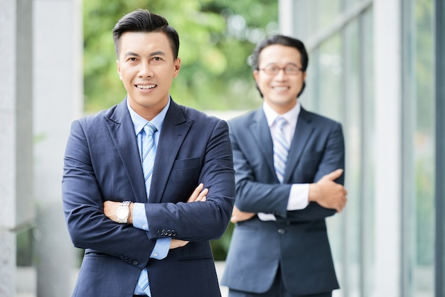 Talia strzelająca dwa azjatyckiego biznesmena stoi z rękami składał outdoors Darmowe Zdjęcia