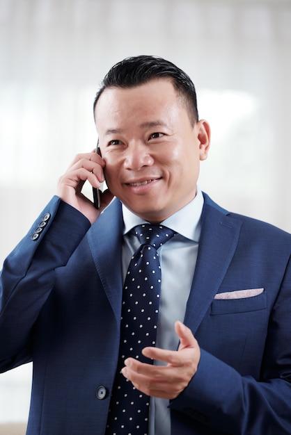 Talia up strzelał azjatycki mężczyzna ma rozmowę telefoniczną z partnerem biznesowym Darmowe Zdjęcia
