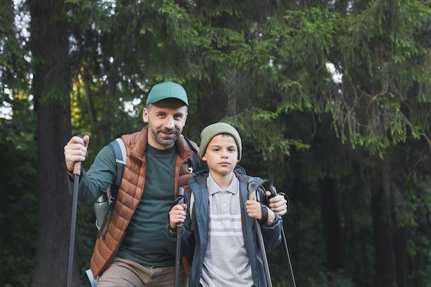 Talia W Górę Portret Szczęśliwego Ojca I Syna Wędrujących Razem I Spacerując Po Lesie Z Kijkami, Skopiuj Miejsce Premium Zdjęcia